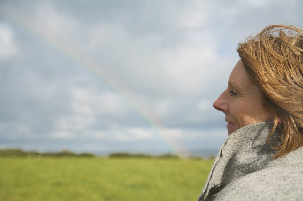 Stock Photo: 4278-4579 Close up of a woman standing in a field looking at the rainbow