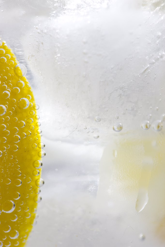 Extreme close up of a slice of lemon floating in sparkling iced water : Stock Photo