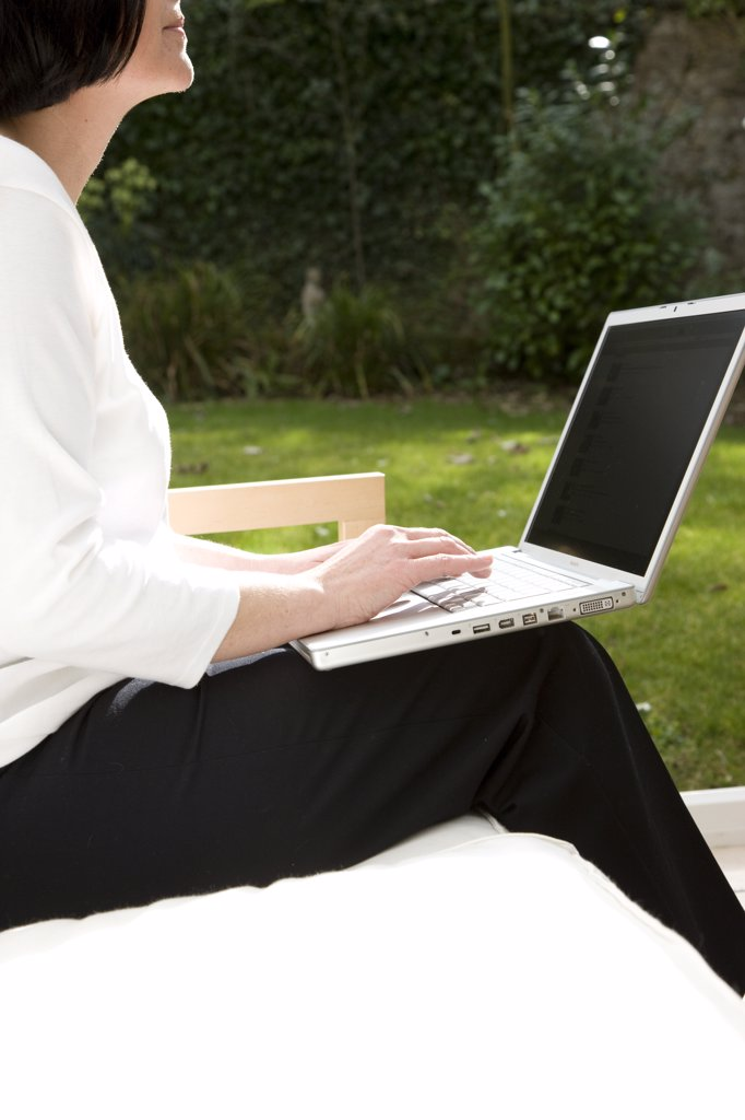 Stock Photo: 4278-4879 Woman sitting and typing on a laptop computer