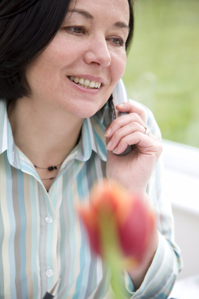 Stock Photo: 4278-4903 Woman talking on a cordless telephone