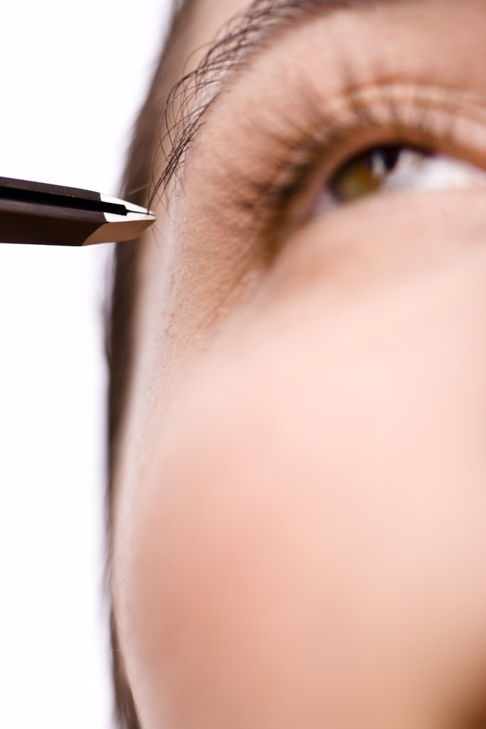 Extreme close up of a woman plucking her eyebrow with tweezers : Stock Photo