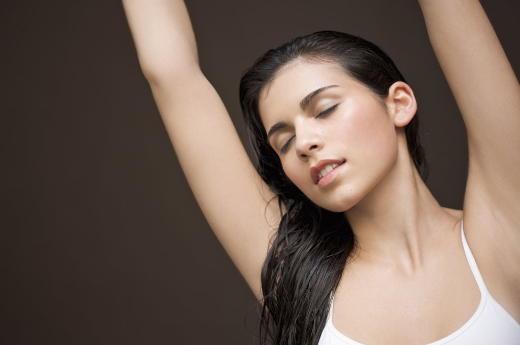 Woman with her arms stretched above her head : Stock Photo