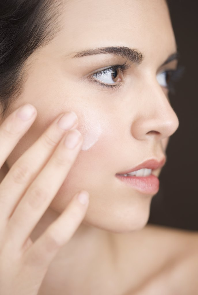 Close up of a woman applying moisturizer on her face : Stock Photo