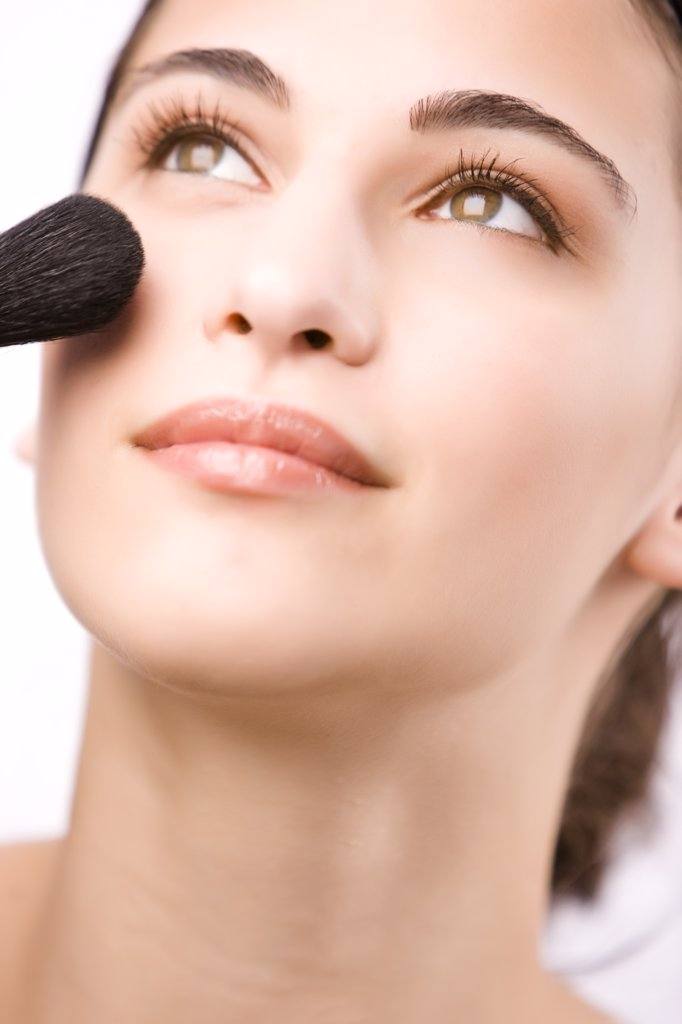 Close up of a young woman applying make with a blush brush : Stock Photo