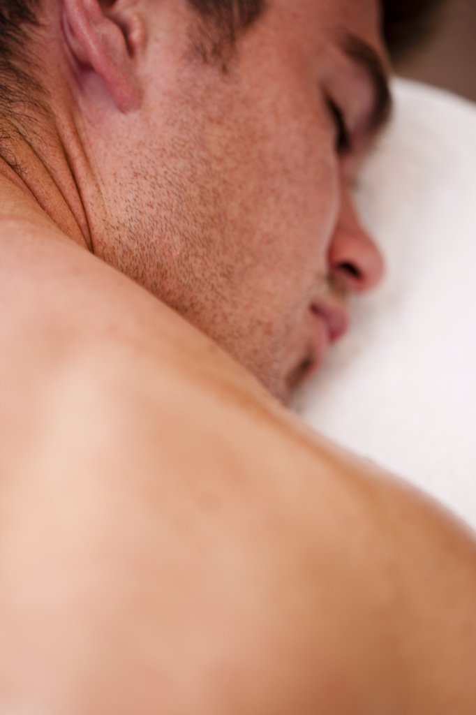 Stock Photo: 4278-5369 Close up of a man lying on his stomach with his eyes closed