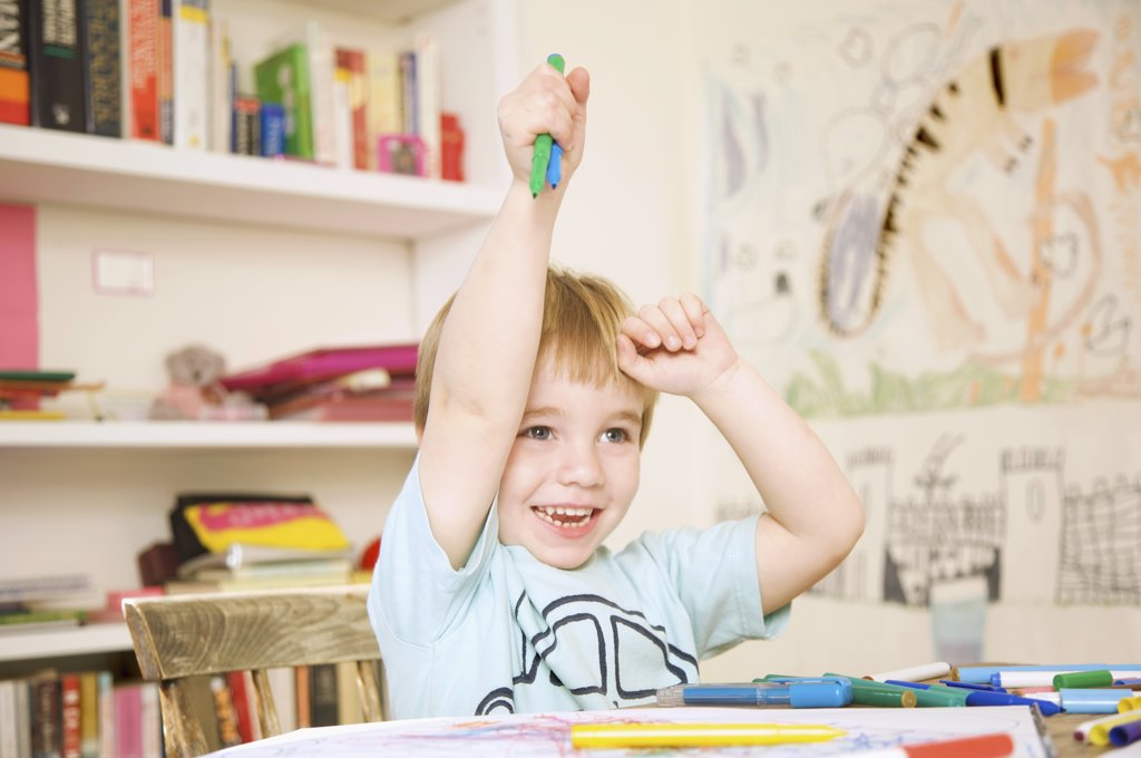 Smiling boy holding coloring pens above his head : Stock Photo