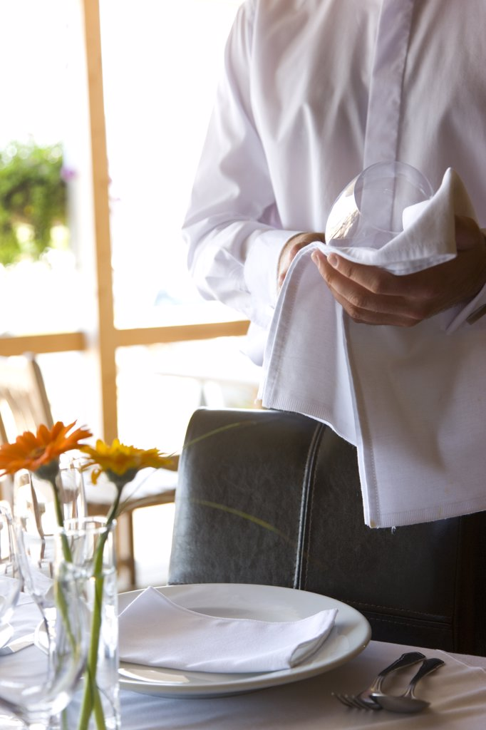 Waiter's hands polishing a wine glass with a napkin : Stock Photo