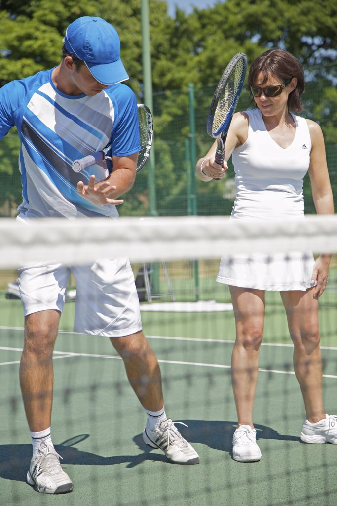 Stock Photo: 4278-5706 Tennis teacher instructing a woman
