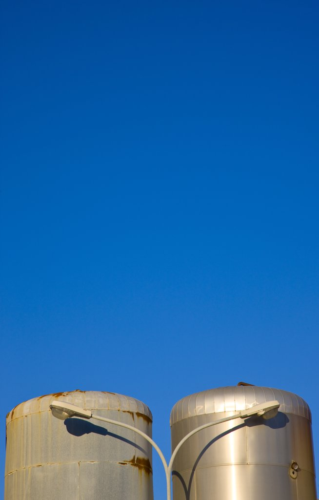 Stock Photo: 4278-5884 Metal storage tanks and lamp post against a cloudless blue sky