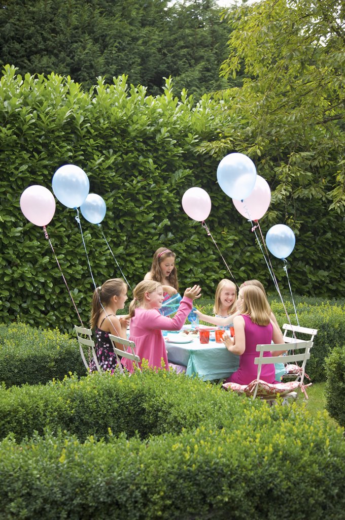 Stock Photo: 4278-5927 Group of young girls having a party in a garden smiling and laughing