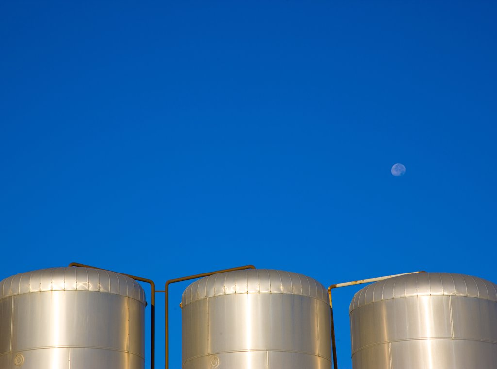 Metal storage tanks against a cloudless blue sky with moon : Stock Photo