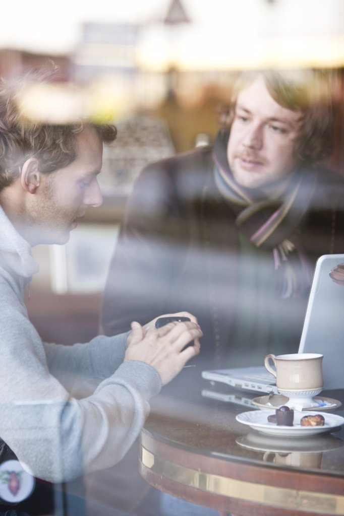 Stock Photo: 4278-6380 Two men talking in a cafe