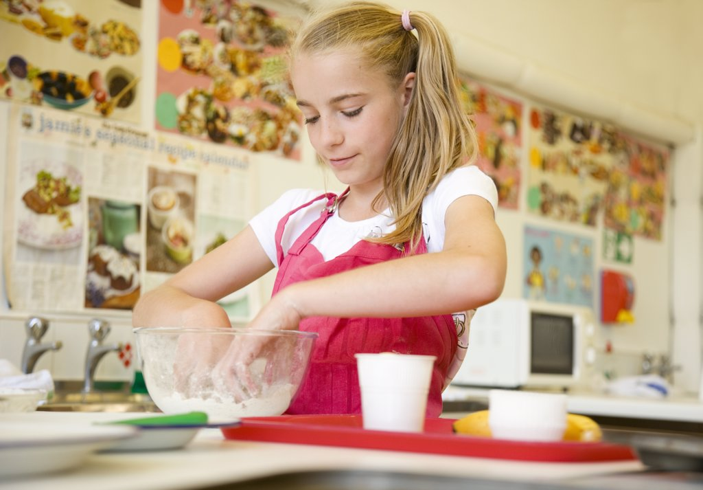 Stock Photo: 4278-6435 Young girl in cookery class kneading