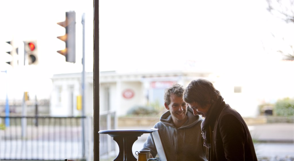 Two men using a laptop in a cafe : Stock Photo