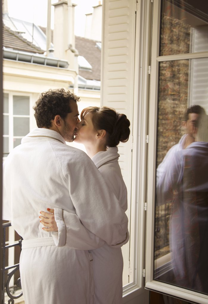 Stock Photo: 4278-6544 Couple kissing in front of an open window