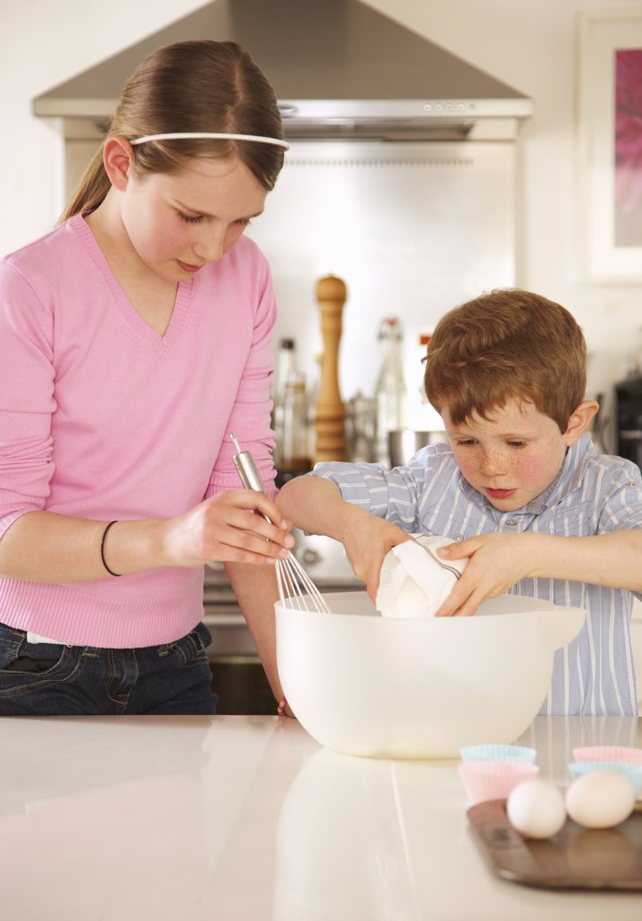 Girl and young boy preparing cupcakes : Stock Photo
