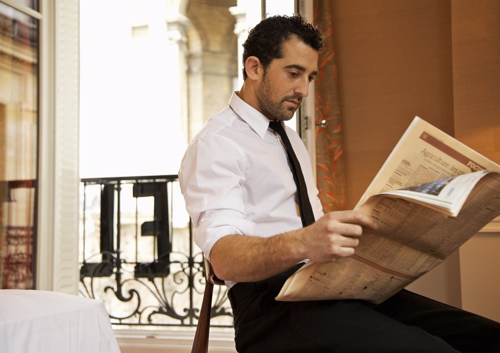 Businessman in hotel room reading newspaper : Stock Photo