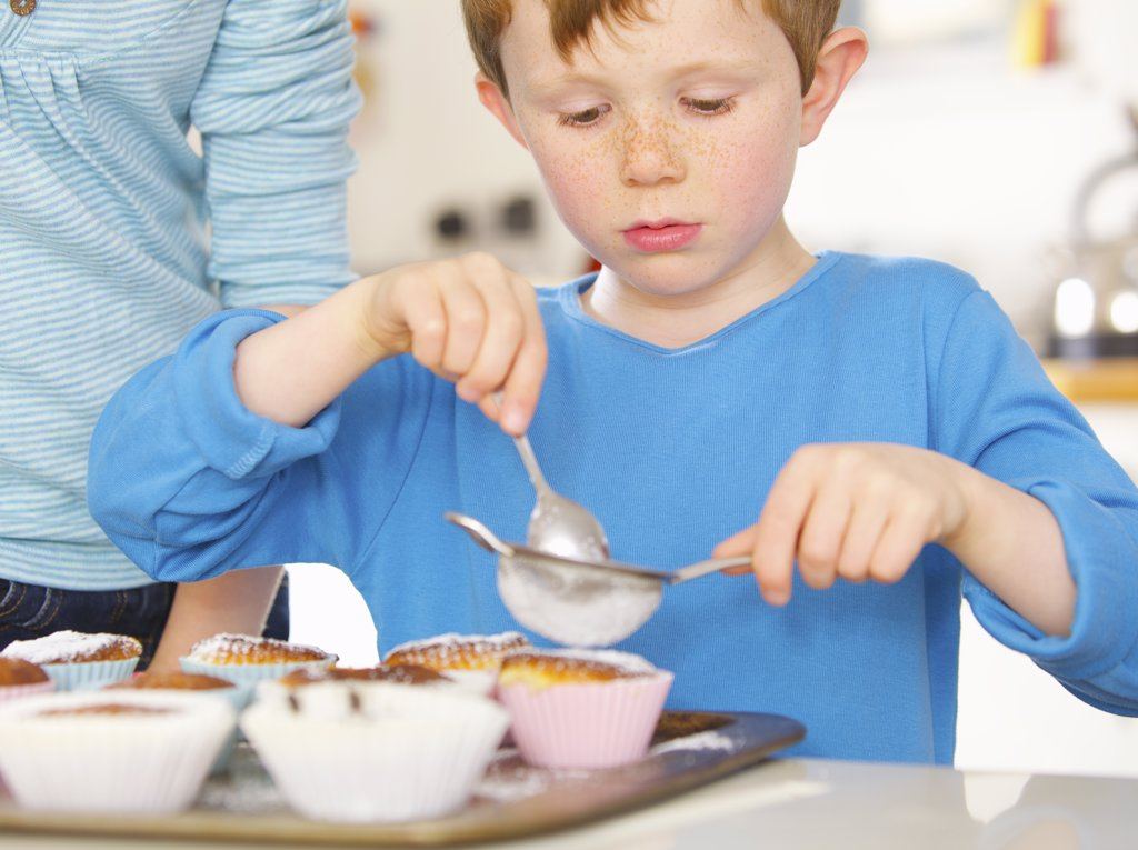Young boy sprinkling cupcakes with icing sugar : Stock Photo