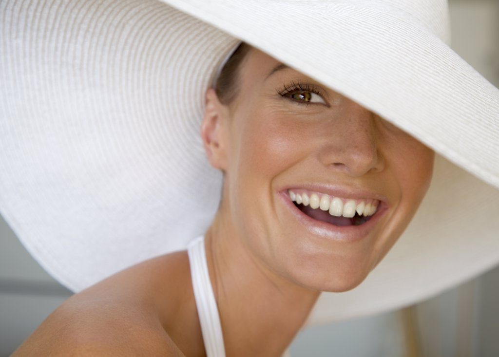Close up of a young woman wearing a white hat smiling : Stock Photo