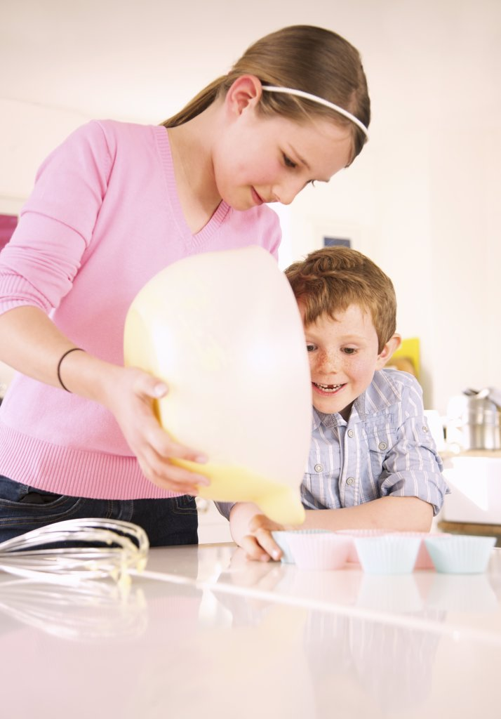 Stock Photo: 4278-6954 Girl and young boy preparing cupcakes