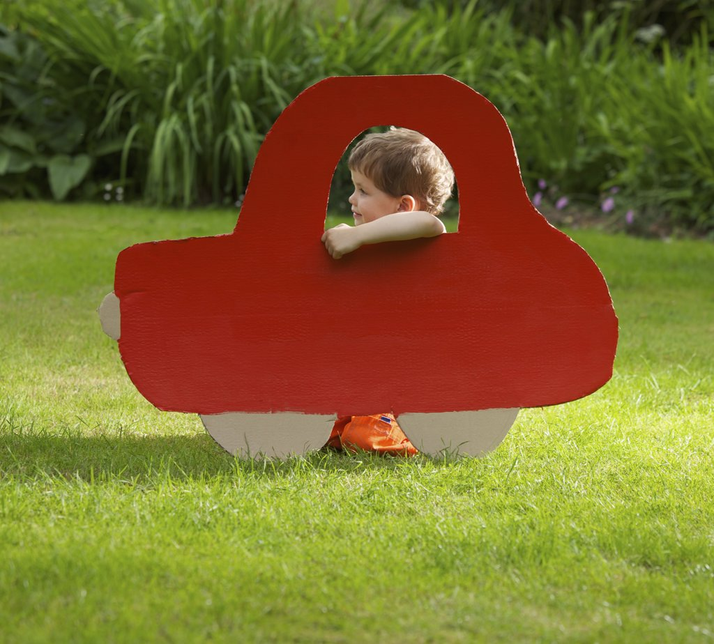 Stock Photo: 4278-7273 Young Boy Kneeling behind Cardboard Cut Out in Shape of Car