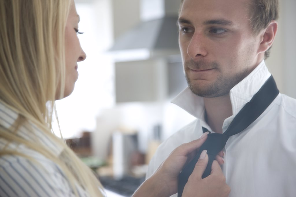 Woman Tying Man's Necktie : Stock Photo