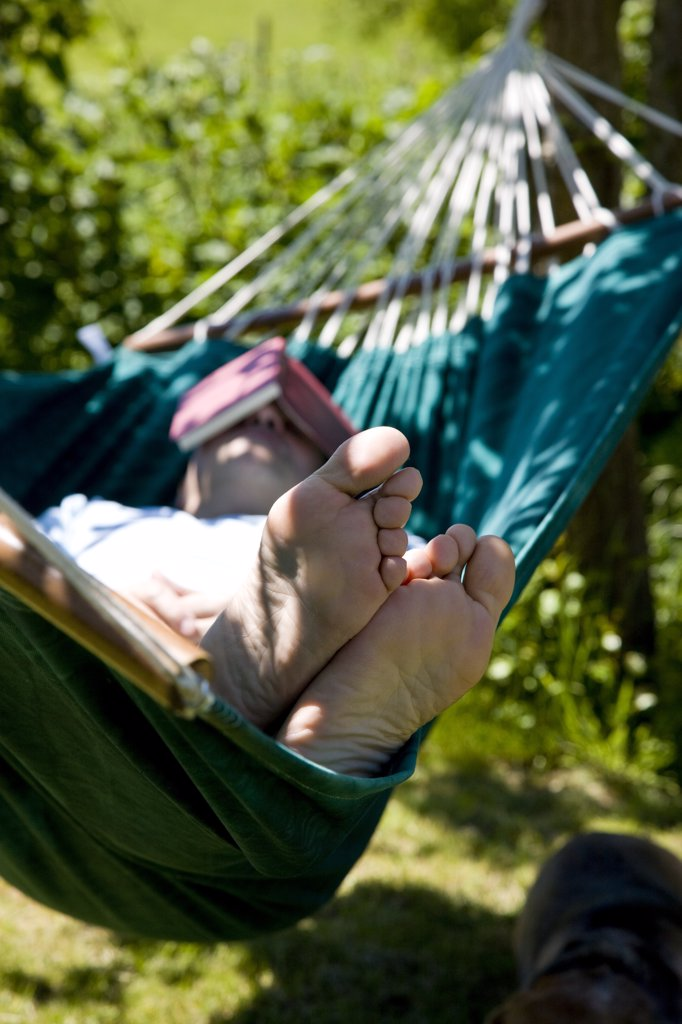 Stock Photo: 4278-7298 Man Sleeping on Hammock with Book over Face