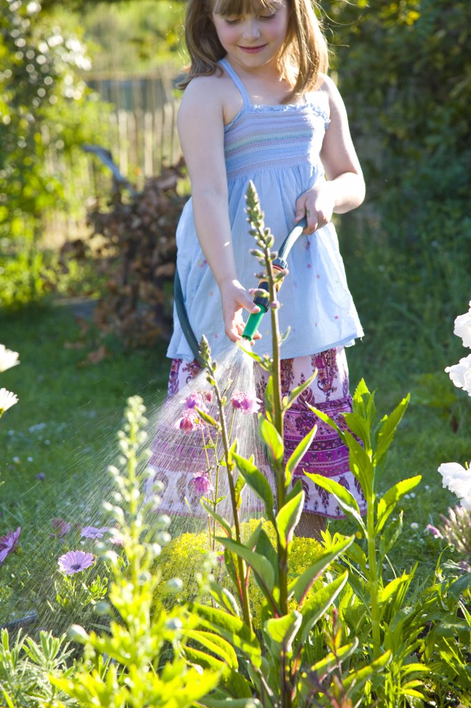 Stock Photo: 4278-7412 Young Girl Watering Flowers with Garden Hose