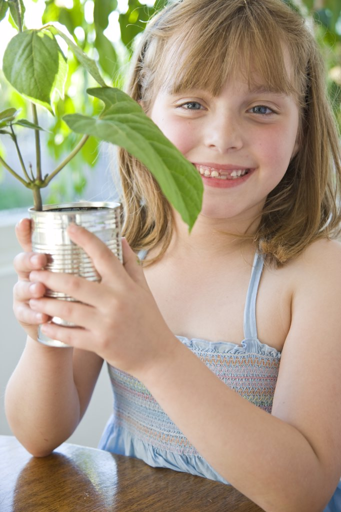 Smiling Girl Holding Plant : Stock Photo