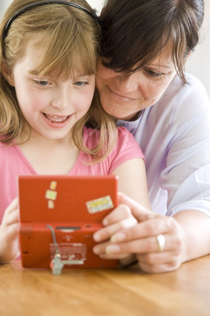 Mother and Daughter Playing with Handheld Video Game : Stock Photo