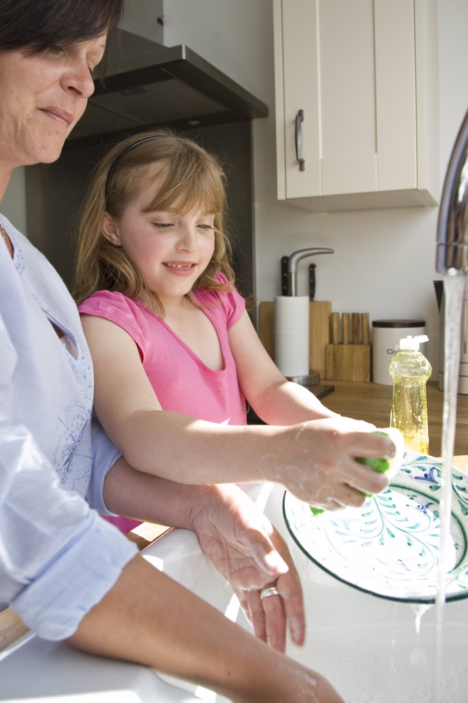 Stock Photo: 4278-7480 Mother and Daughter Washing Dishes