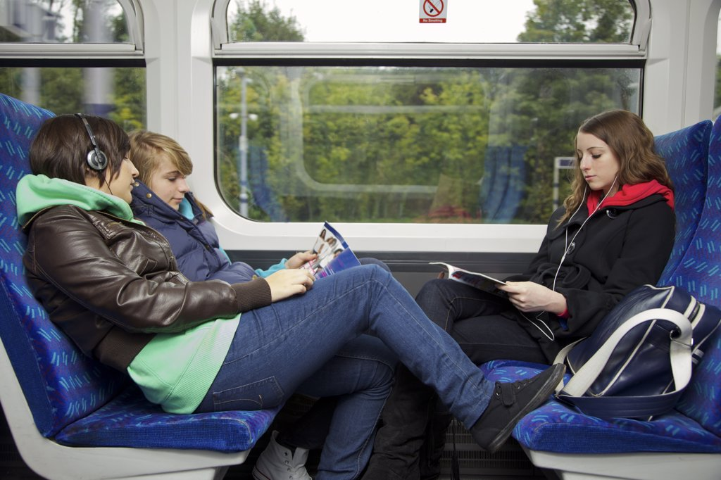 Stock Photo: 4278-7483 Teenage Girls Sitting on Train Reading and Listening to Music