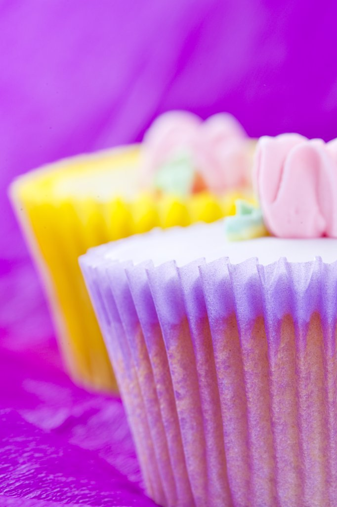 Stock Photo: 4278-7488 Pink and  Yellow Cupcakes with Pastel Pink Flower Decoration