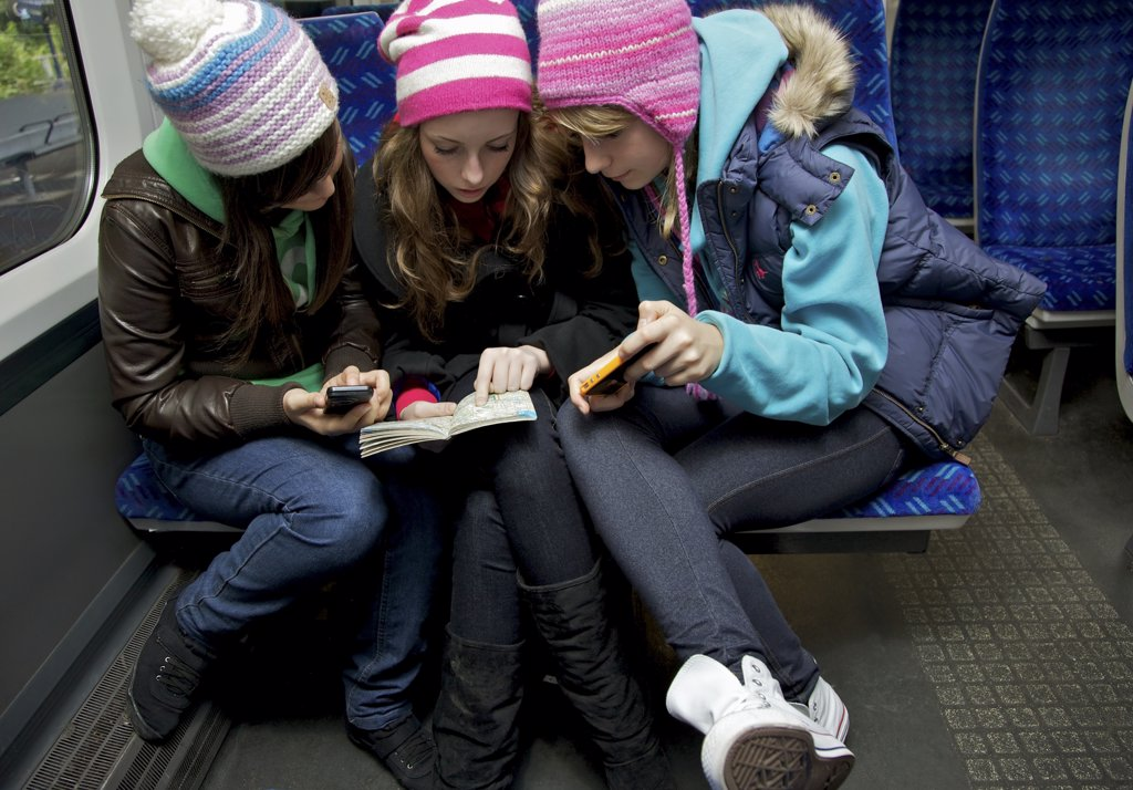 Teenage Girls Sitting on Train Inspecting a Guidebook : Stock Photo