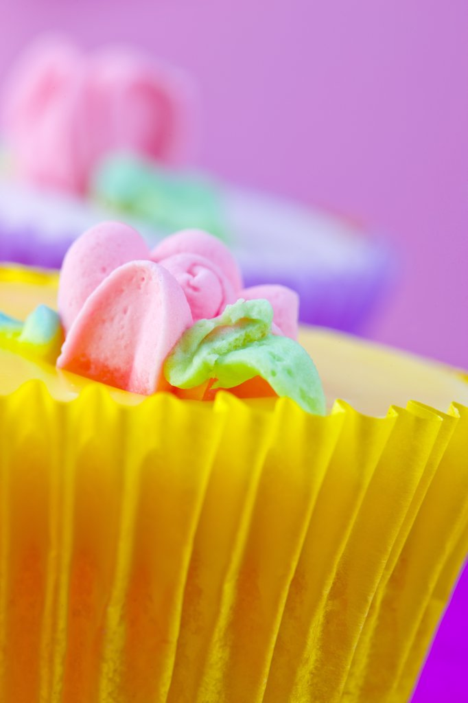 Bright Yellow Cupcake with Pastel Pink Flower Decoration : Stock Photo