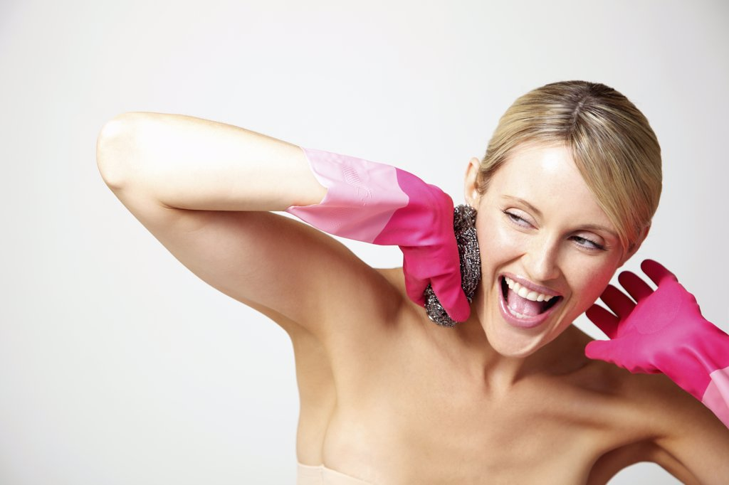 Stock Photo: 4278-7578 Woman Wearing Bright Pink Rubber Gloves Holding Pan Scourer against Face