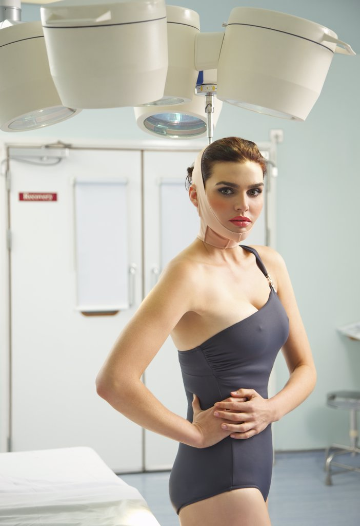 Woman with Elastic Bandage on Face Standing under Surgical Lamp : Stock Photo