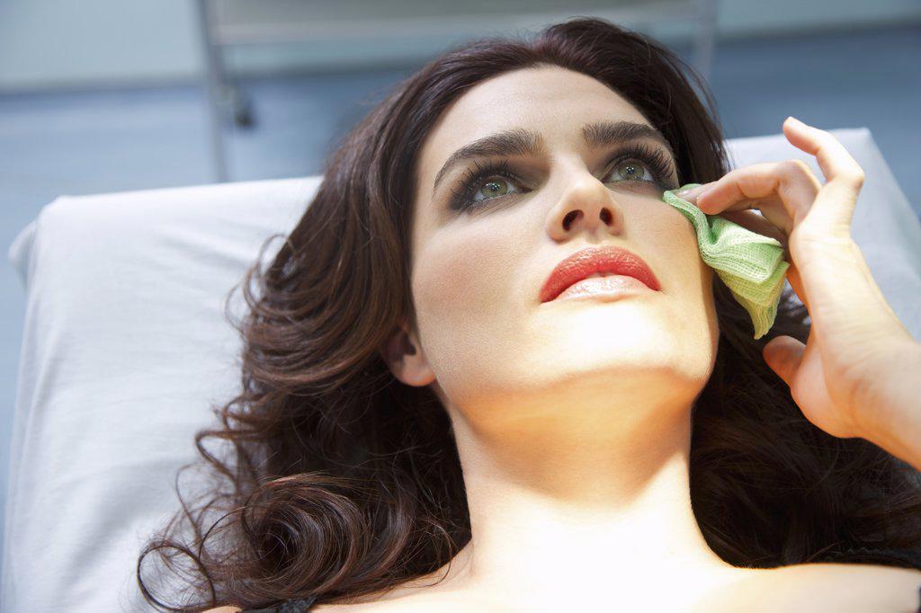 Stock Photo: 4278-7700 Woman's Wiping Corner of Eye with Green Gauze