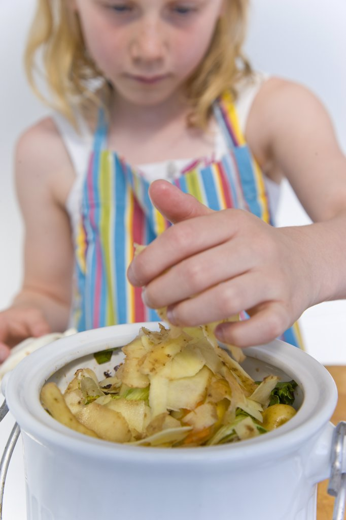 Girl Discarding Potatoes Skins into a Kitchen Compost Container : Stock Photo