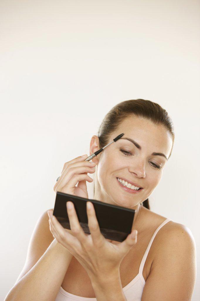 Stock Photo: 4278-8171 Woman Holding Handheld Mirror Using Eyebrow Brush