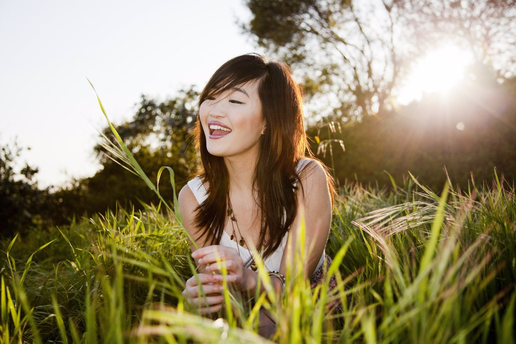 Stock Photo: 4278-8276 Smiling Young Woman In a Field