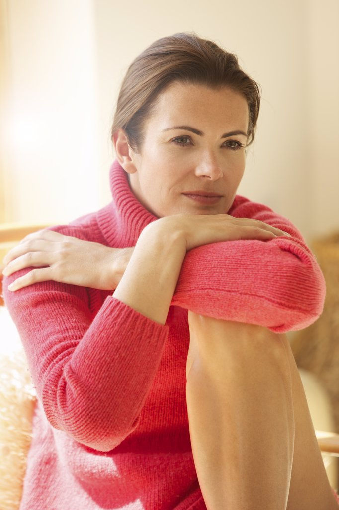 Woman with Arms Crossed and Face Resting on One Knee : Stock Photo