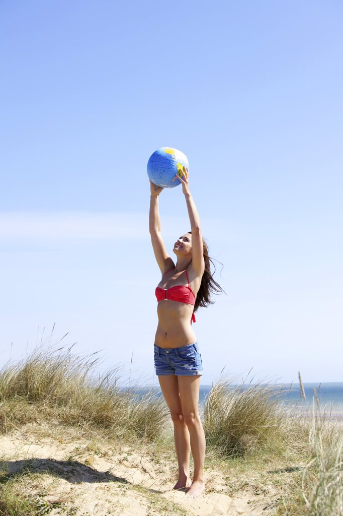 Stock Photo: 4278-8403 Woman Holding Ball above Head at Beach