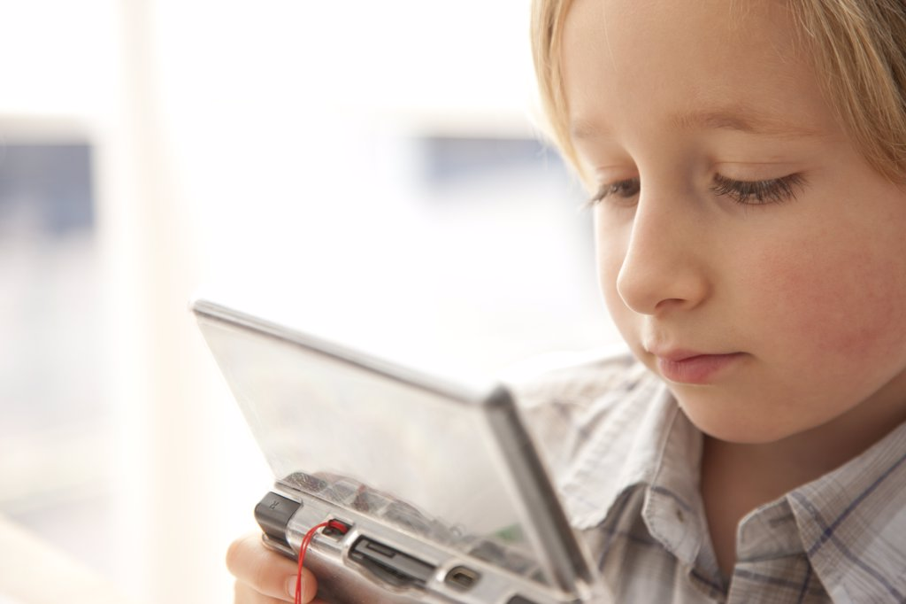 Boy Playing with Handheld Video Game : Stock Photo