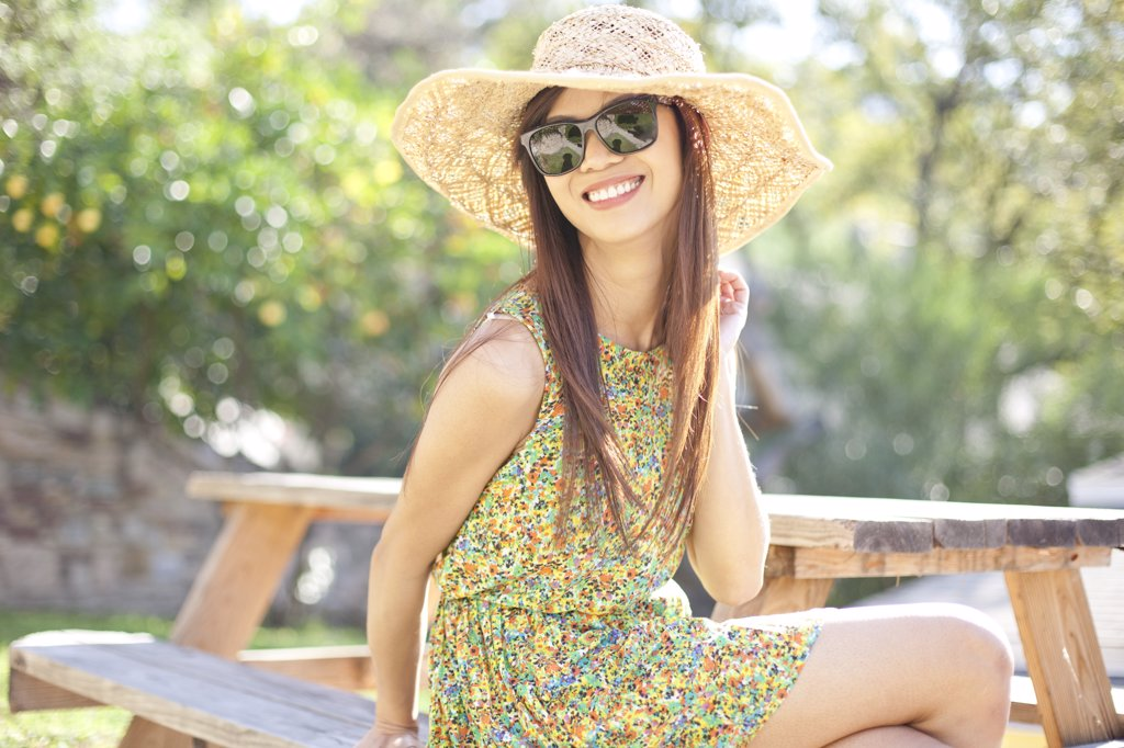Smiling Woman Wearing Straw Hat Sitting on Picnic Table : Stock Photo