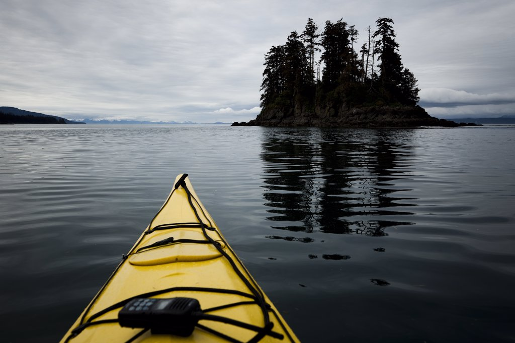Stock Photo: 4278-9298 Bow of Yellow Kayak with Walkie-Talkie Moving towards Small Island