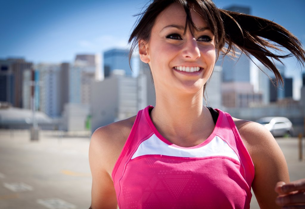 Stock Photo: 4278-9551 Smiling Young Woman Running Outdoors