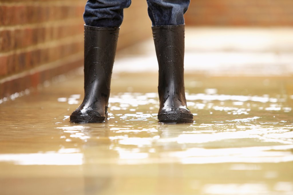 Boy's Legs in Wellington Boots on Flooded Pavement : Stock Photo