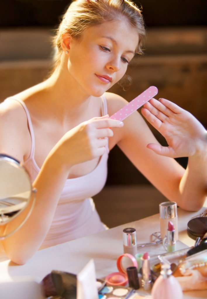 Young Woman Filing her Nails at Dressing Table : Stock Photo