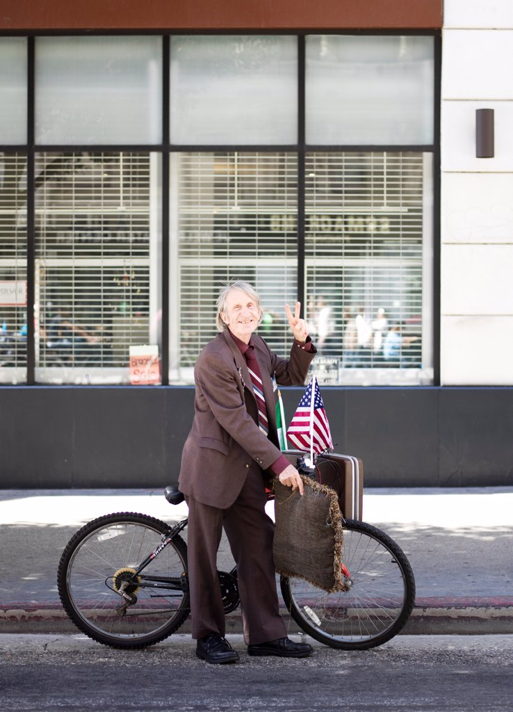 Stock Photo: 4278-9601 Senior Man with Bicycle Making Peace Sign